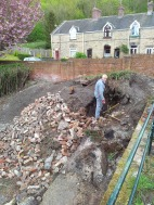 John pauses for a moment whilst digging through the rubble.