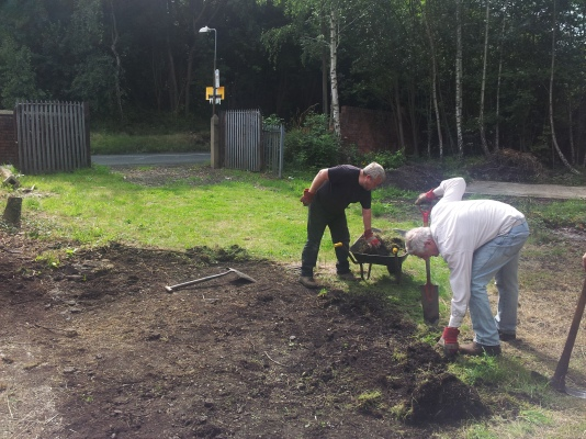Lifting the grass and removing roots; the entrance gates beyond