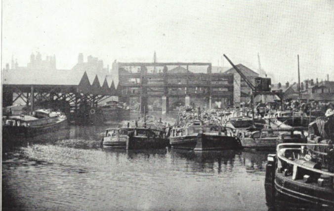 Busy canal wharf scene with barges loading and unloading