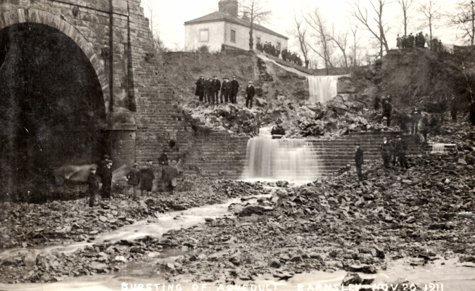 Photographic postcard of the burst abutment of the aqueduct of the Barnsley Canal, with spectators viewing the damage as water pours down the breached stone.