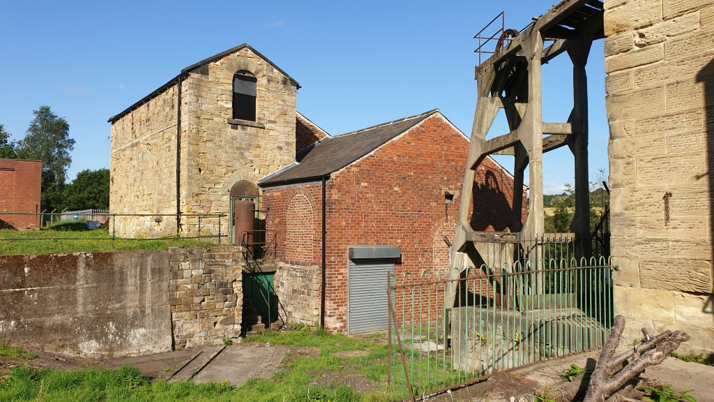 View of the winding engine house and pay off the pumping shaft and headgear next to it.